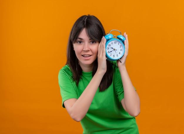 Lieta giovane ragazza caucasica in camicia verde tiene l'orologio con entrambe le mani su sfondo arancione isolato