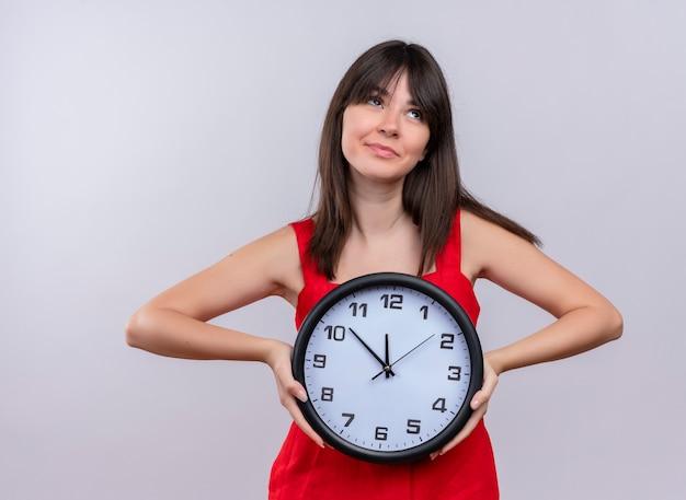 Lieta giovane ragazza caucasica tenendo l'orologio con entrambe le mani e alzando lo sguardo su sfondo bianco isolato