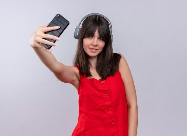 電話を持って、孤立した白い背景の上のヘッドフォンで電話を見て喜んで若い白人の女の子