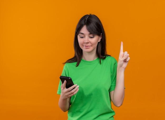 Довольная молодая кавказская девушка в зеленой рубашке держит телефон и указывает на изолированный оранжевый фон с копией пространства