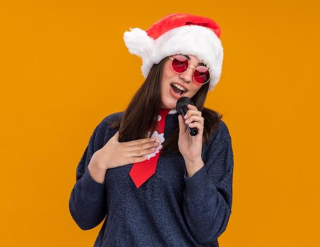 Довольная молодая кавказская девушка в солнцезащитных очках с новогодней шапкой и новогодним галстуком кладет руку на грудь и держит микрофон, делая вид, что поет