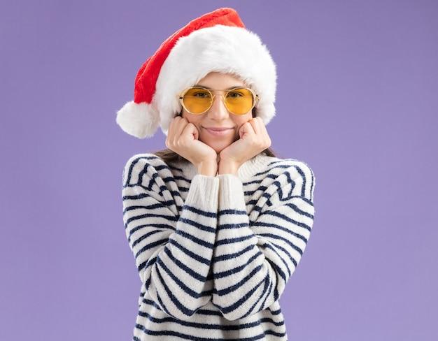 산타 모자와 태양 안경에 만족 된 젊은 백인 여자는 얼굴에 손을 둔다
