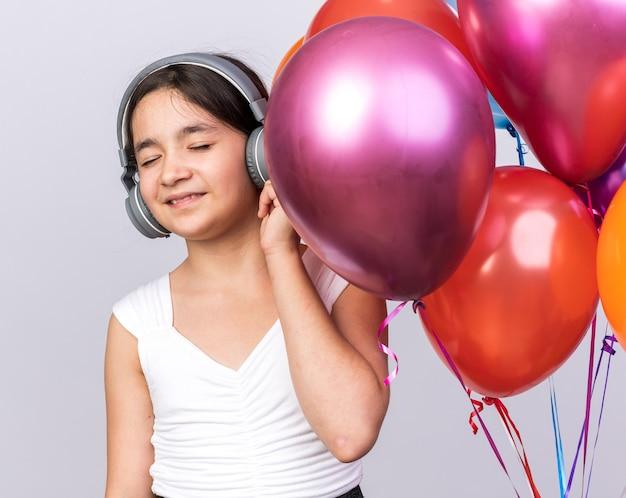 Довольная молодая кавказская девушка в наушниках, стоя с гелиевыми шарами, изолированными на белой стене с копией пространства