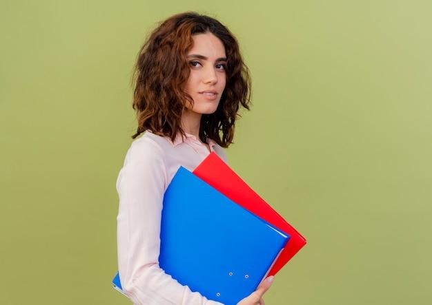 Lieta giovane ragazza caucasica si trova lateralmente tenendo le cartelle di file isolate su sfondo verde con spazio di copia