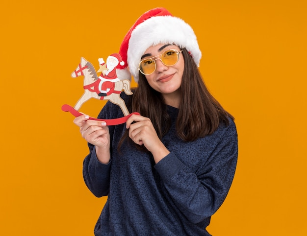 Pleased young caucasian girl in sun glasses with santa hat holds santa on rocking horse decoration