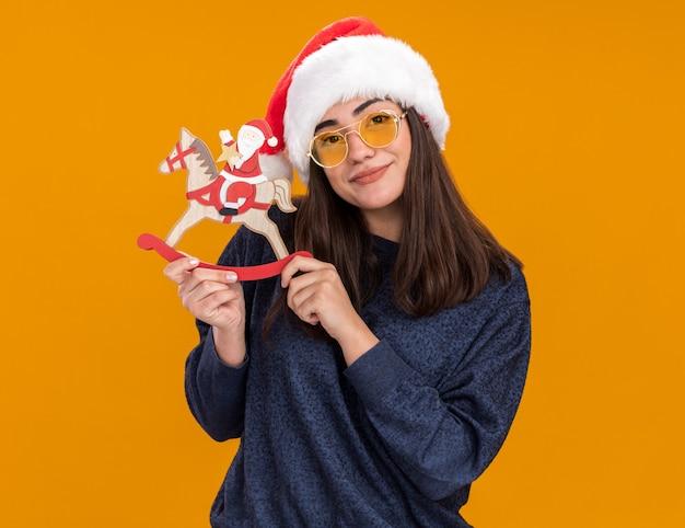 Lieta giovane ragazza caucasica in occhiali da sole con cappello santa tiene santa sulla decorazione del cavallo a dondolo