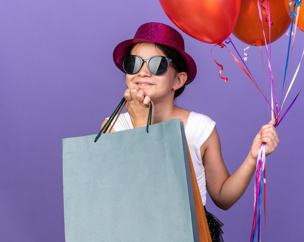 Pleased young caucasian girl in sun glasses with violet party hat putting hand on chin holding helium balloons and shopping bags isolated on purple wall with copy space