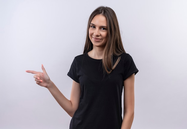 Довольная молодая кавказская девушка в черной футболке указывает в сторону на изолированной белой стене