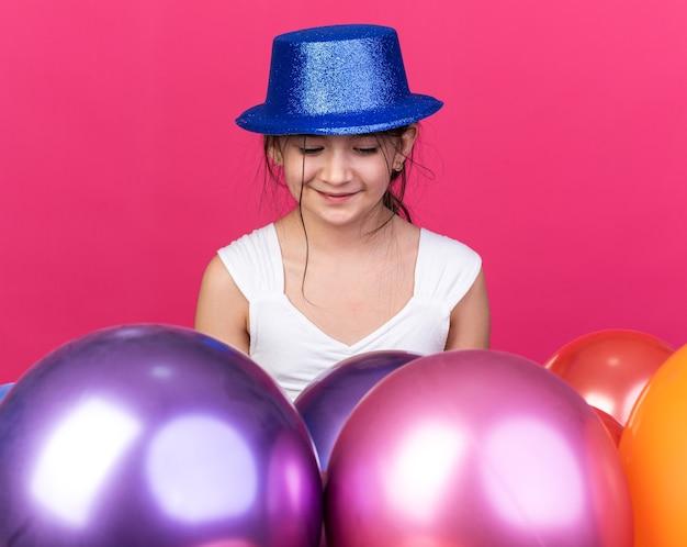 헬륨 풍선으로 서서 복사 공간이 분홍색 벽에 고립 된 찾고 파란색 파티 모자를 쓰고 기쁘게 젊은 백인 여자