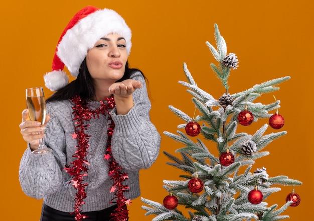 Compiaciuta giovane ragazza caucasica che indossa cappello di natale e ghirlanda di orpelli intorno al collo in piedi vicino a un albero di natale decorato con in mano un bicchiere di champagne invio di un bacio isolato sulla parete arancione