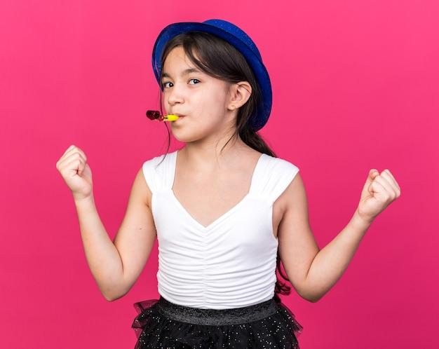 Довольная молодая кавказская девушка в синей партийной шляпе дует в свисток и держит кулаки на розовой стене с копией пространства