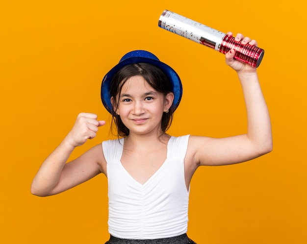 Pleased young caucasian girl with blue party hat holding confetti cannon and keeping fist up isolated on orange wall with copy space