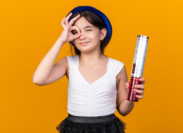 Pleased young caucasian girl with blue party hat holding confetti cannon and  through fingers isolated on orange wall with copy space
