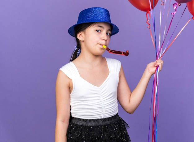 Pleased young caucasian girl with blue party hat holding helium balloons and blowing party whistle isolated on purple wall with copy space