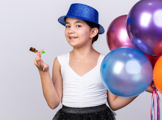 Pleased young caucasian girl with blue party hat holding helium balloons and party whistle isolated on white wall with copy space