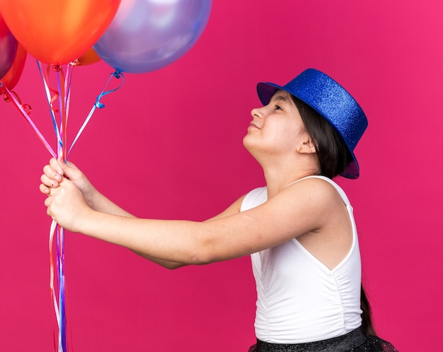 Pleased young caucasian girl with blue party hat holding and looking at helium balloons isolated on pink wall with copy space