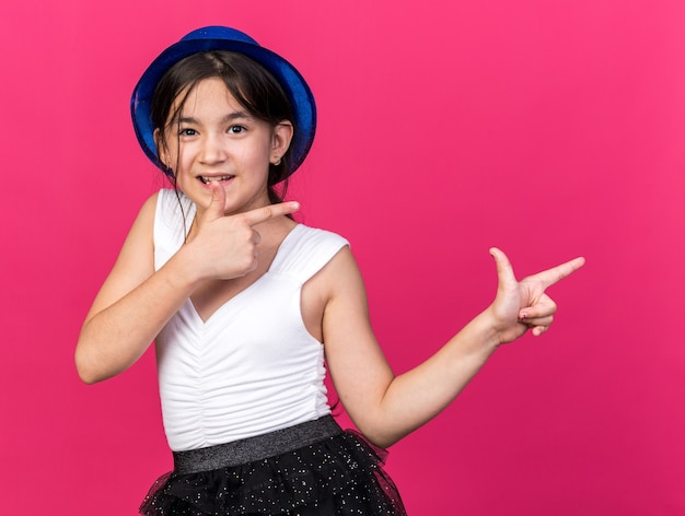Pleased young caucasian girl with blue party hat pointing at side isolated on pink wall with copy space