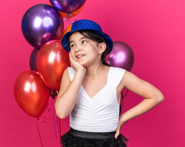 Pleased young caucasian girl with blue party hat putting hand on face and looking at side standing in front of helium balloons isolated on pink wall with copy space