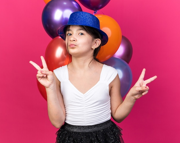 Pleased young caucasian girl with blue party hat standing in front of helium balloons gesturing victory sign isolated on pink wall with copy space