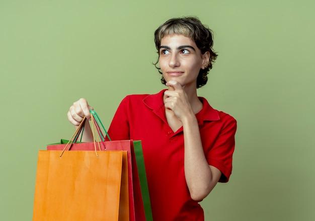 コピースペースでオリーブグリーンの背景に分離された側を見てあごに触れて買い物袋を保持しているピクシーヘアカットで満足している若い白人の女の子