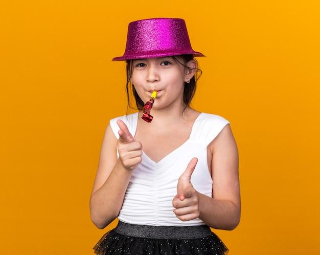 Довольная молодая кавказская девушка с фиолетовой шляпой дует свисток и указывает на оранжевую стену с копией пространства