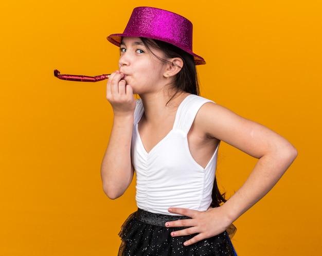 Довольная молодая кавказская девушка с фиолетовой шляпой дует свисток на оранжевой стене с копией пространства