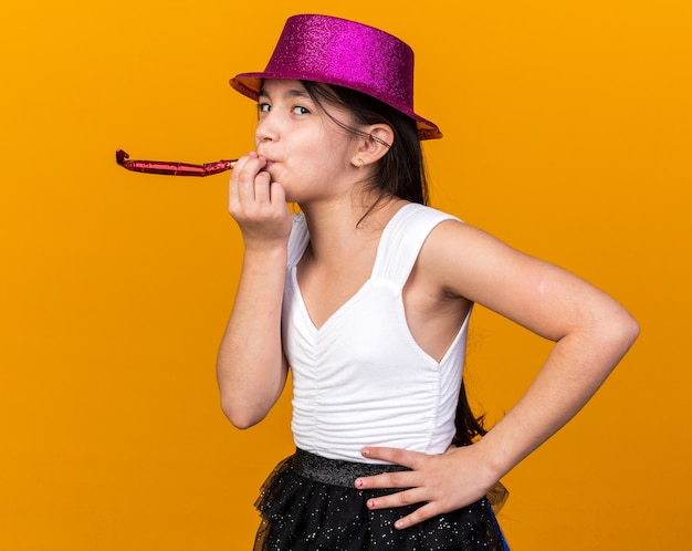 Pleased young caucasian girl with purple party hat blowing party whistle isolated on orange wall with copy space