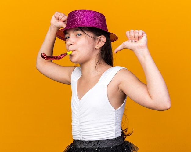 Pleased young caucasian girl with purple party hat blowing party whistle and pointing at herself isolated on orange wall with copy space
