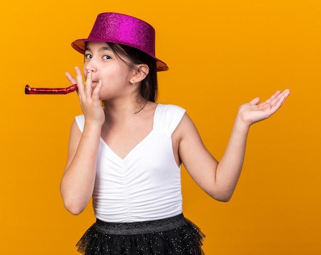 コピースペースとオレンジ色の壁に分離された上げられた手で立っている紫色のパーティーハット吹くパーティー笛で喜んで若い白人の女の子
