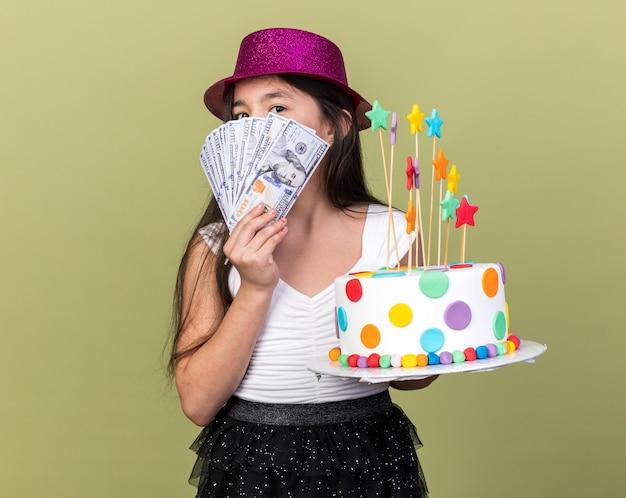 コピースペースでオリーブグリーンの壁に分離されたバースデーケーキとお金を保持している紫色のパーティハットを持つ白人の少女を喜ばせ