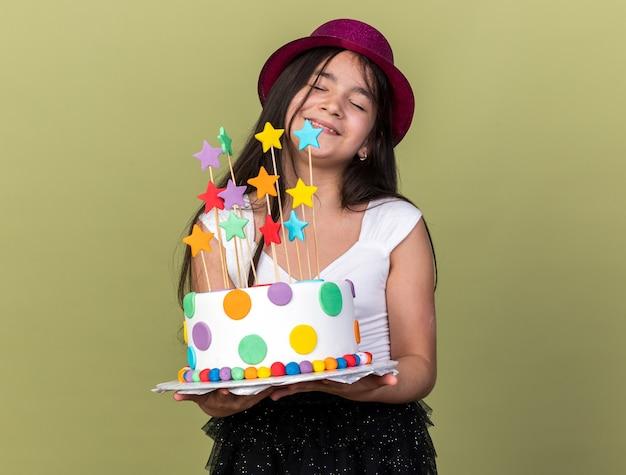 コピースペースでオリーブグリーンの壁に分離されたバースデーケーキを保持している紫色のパーティーハットを持つ白人の少女を喜ばせ