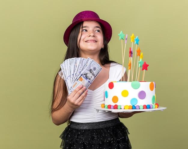 Felice giovane ragazza caucasica con viola party hat tenendo la torta di compleanno e denaro guardando il lato isolato su verde oliva parete con spazio di copia