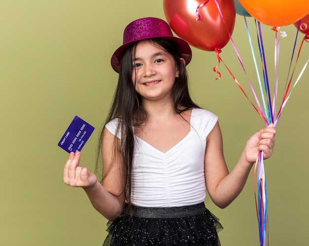 Pleased young caucasian girl with purple party hat holding credit card and helium balloons isolated on olive green wall with copy space