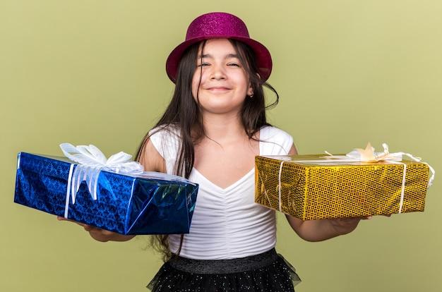 Contenta giovane ragazza caucasica con cappello da festa viola che tiene una confezione regalo su ogni mano isolata sulla parete verde oliva con spazio di copia