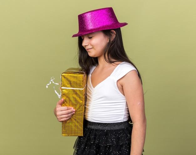 Довольная молодая кавказская девушка в фиолетовой шляпе держит подарочную коробку, изолированную на оливково-зеленой стене с копией пространства