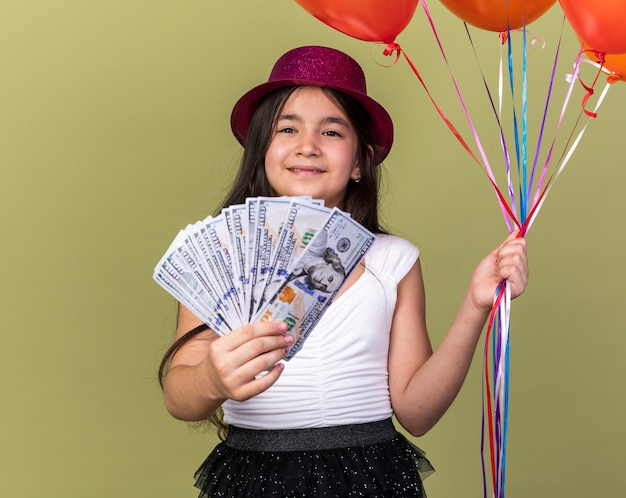 コピースペースのあるオリーブグリーンの壁に隔離されたヘリウム気球とお金を保持している紫色のパーティハットで喜んで若い白人の女の子