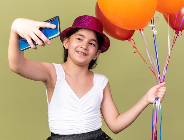 Довольная молодая кавказская девушка с фиолетовой шляпой держит гелиевые шары и делает селфи по телефону, изолированному на оливково-зеленой стене с копией пространства
