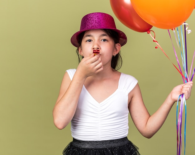 Pleased young caucasian girl with purple party hat holding helium balloons and blowing party whistle isolated on olive green wall with copy space