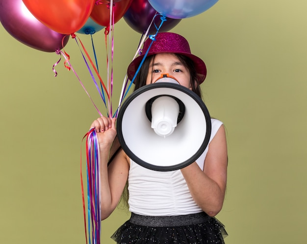 Pleased young caucasian girl with purple party hat holding helium balloons and loud speaker isolated on olive green wall with copy space