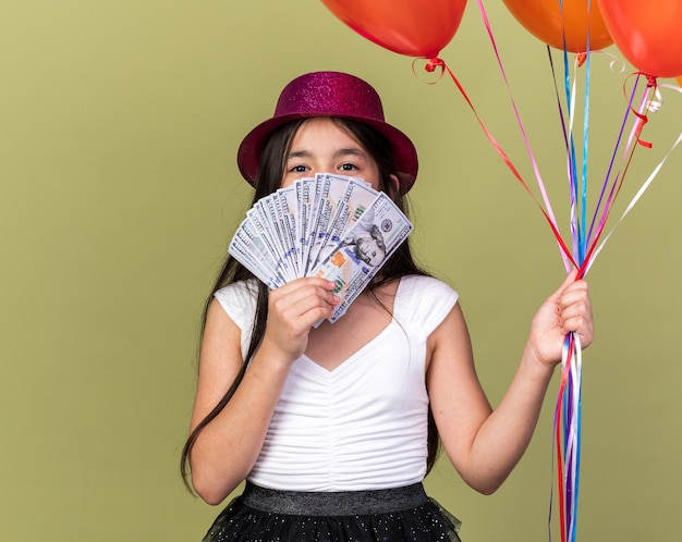 Pleased young caucasian girl with purple party hat holding helium balloons and money in front of her face isolated on olive green wall with copy space