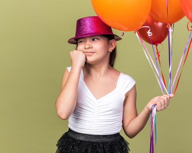 Felice giovane ragazza caucasica con cappello da festa viola che tiene palloncini di elio mettendo il pugno sul viso e guardando il lato isolato sulla parete verde oliva con spazio di copia