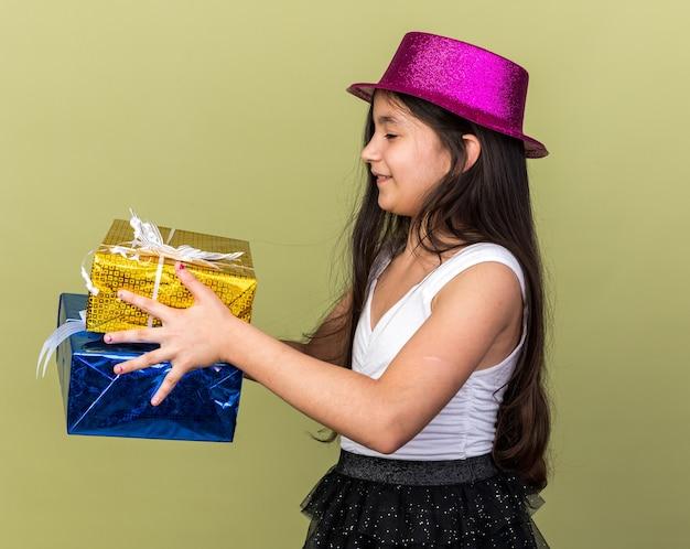 Contenta giovane ragazza caucasica con cappello da festa viola che tiene e guarda scatole regalo isolate su parete verde oliva con spazio di copia