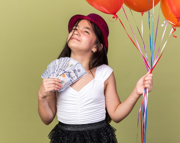 Lieta giovane ragazza caucasica con cappello da festa viola che tiene i palloncini di denaro ed elio che osserva in su isolato sulla parete verde oliva con lo spazio della copia