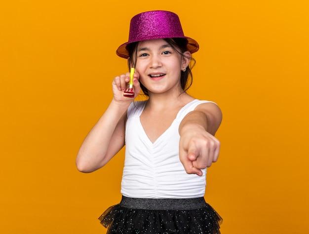 Довольная молодая кавказская девушка с фиолетовой шляпой держит партийный свисток и указывает на оранжевую стену с копией пространства
