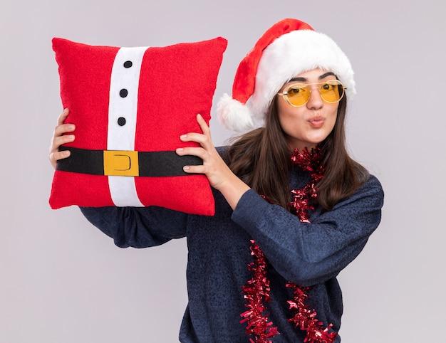 首の周りにサンタの帽子と花輪を持つ満足している若い白人の女の子は、コピースペースで白い壁に分離された装飾された枕を保持します