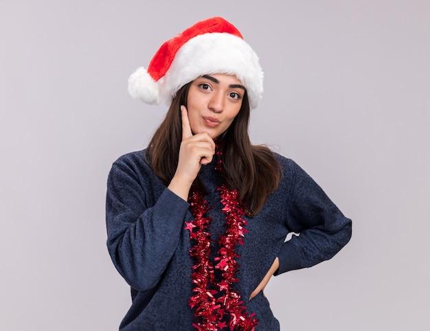 サンタの帽子と首に花輪を持つ満足している若い白人の女の子は、あごに指を置き、見えます