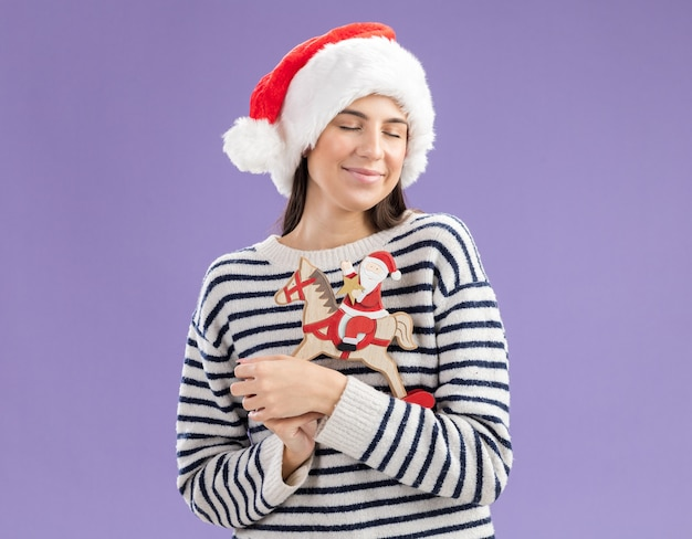 Pleased young caucasian girl with santa hat holding santa on rocking horse decoration