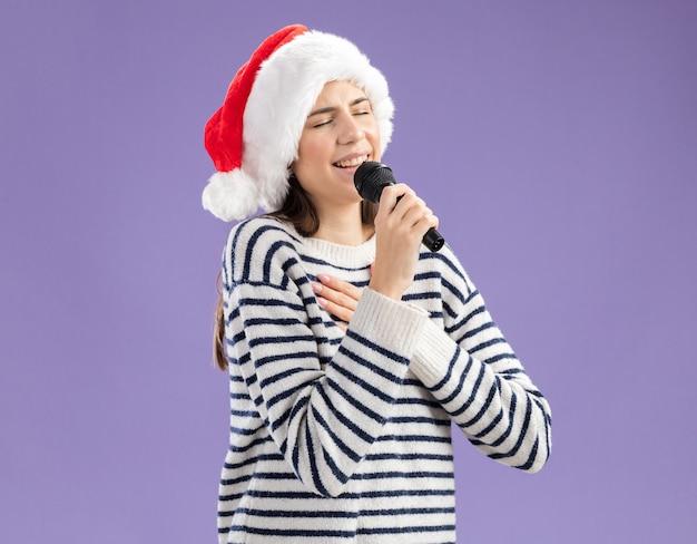 Довольная молодая кавказская девушка в новогодней шапке держит микрофон, делая вид, что поет, и кладет руку на грудь