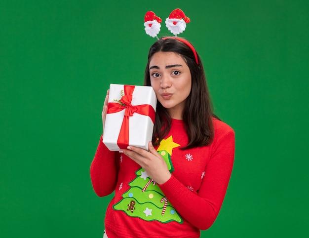 Довольная молодая кавказская девушка с ободком санта-клауса держит рождественскую подарочную коробку на зеленом фоне с копией пространства