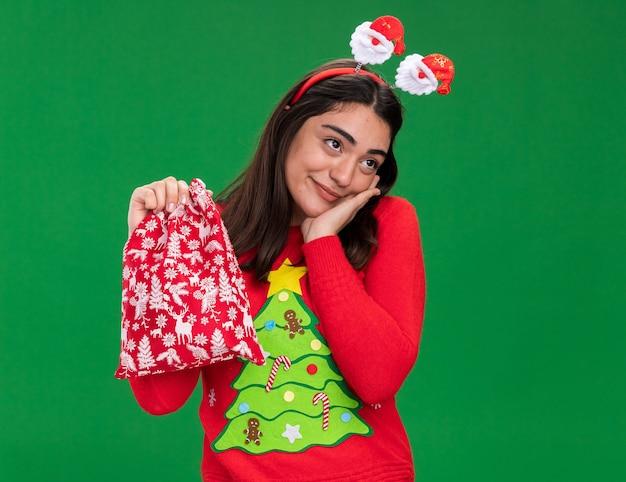 サンタのヘッドバンドで喜んで若い白人の女の子が顔に手を置き、コピースペースで緑の背景に分離されたクリスマスギフトバッグを保持